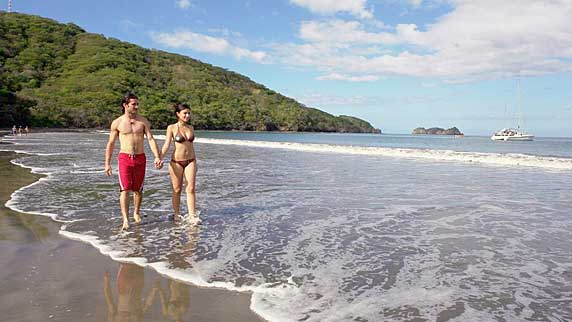 Costa Rica Honeymoon couple walking along beach hand in hand