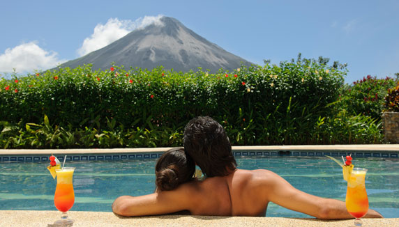 Couple in the pool with cocktails enjoying the view of Arenal Volcano