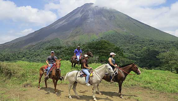 People horse riding with Arenal volcano in the background